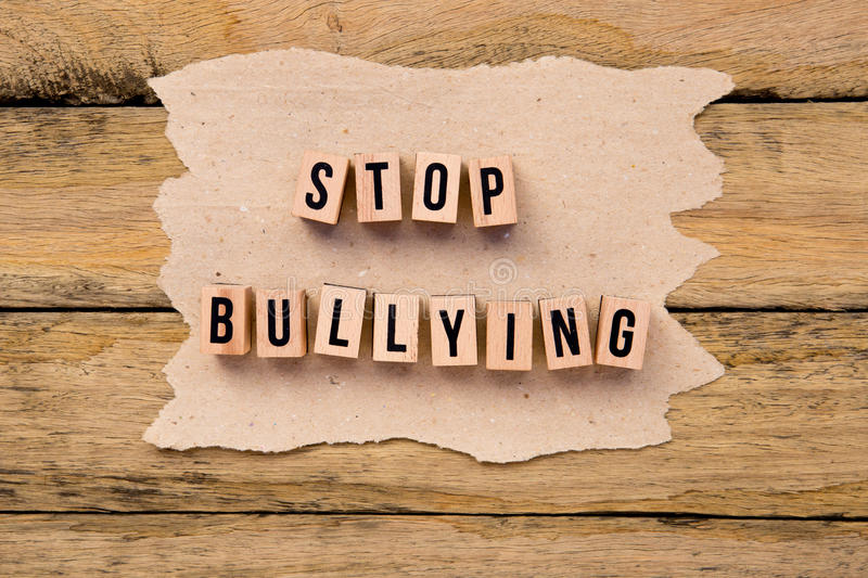 Stop Bullying - in wooden letters on torn handmade paper on wood stock image