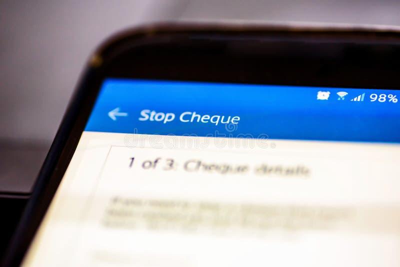 Stop a cheque button on smartphone app screen closeup stock photo
