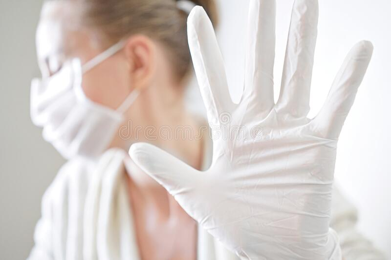 Stop corona virus covid-19 pandemic. woman in white medical protective mask and gloves showing gesture stop. Health protection and prevention during flu and stock image