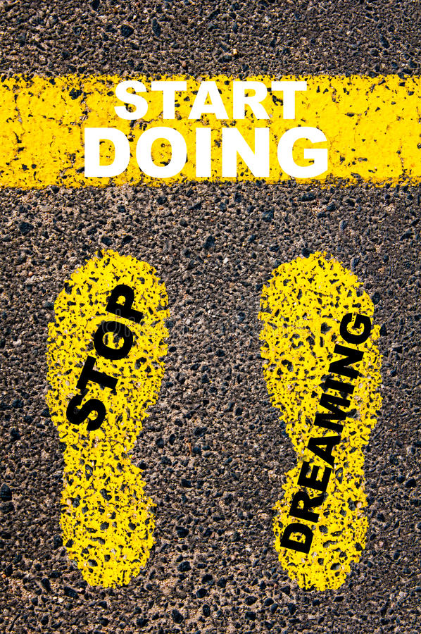 Stop Dreaming Start Doing Message. Conceptual image. With yellow paint footsteps on the road in front of horizontal line over asphalt stone background royalty free stock photo