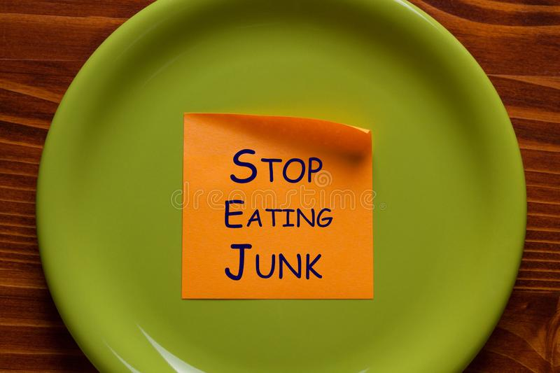 Stop Eating Junk. Written on note in plate. Eat concept royalty free stock photos