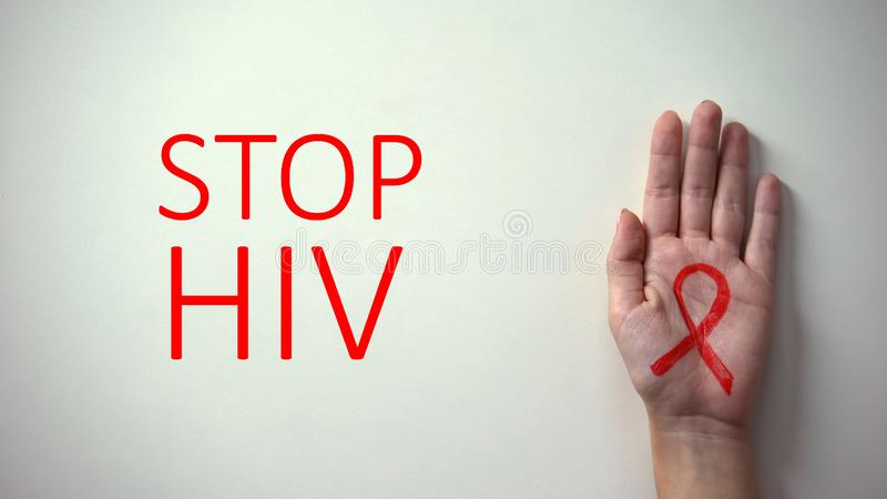 Stop HIV inscription, hand with red ribbon, awareness and prevention campaign stock image