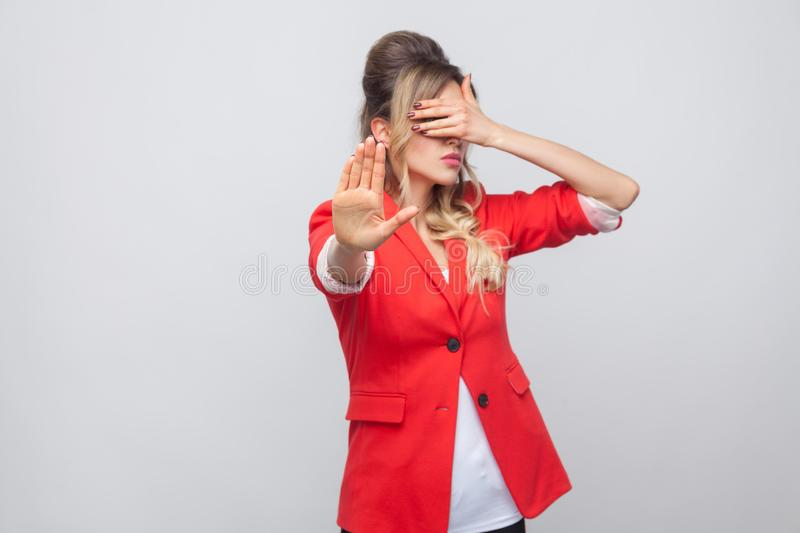 Stop, i dont want to see this. Portrait of beautiful business lady with hairstyle and makeup in red fancy blazer, standing. Covering her eyes with stop hands stock image