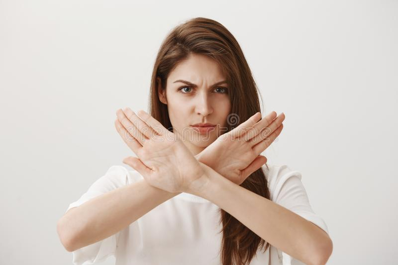 Stop, I hate such attitude. Portrait of angry displeased attractive european girl showing stop, no or dislike gesture. With crossed arms, frowning and being stock images