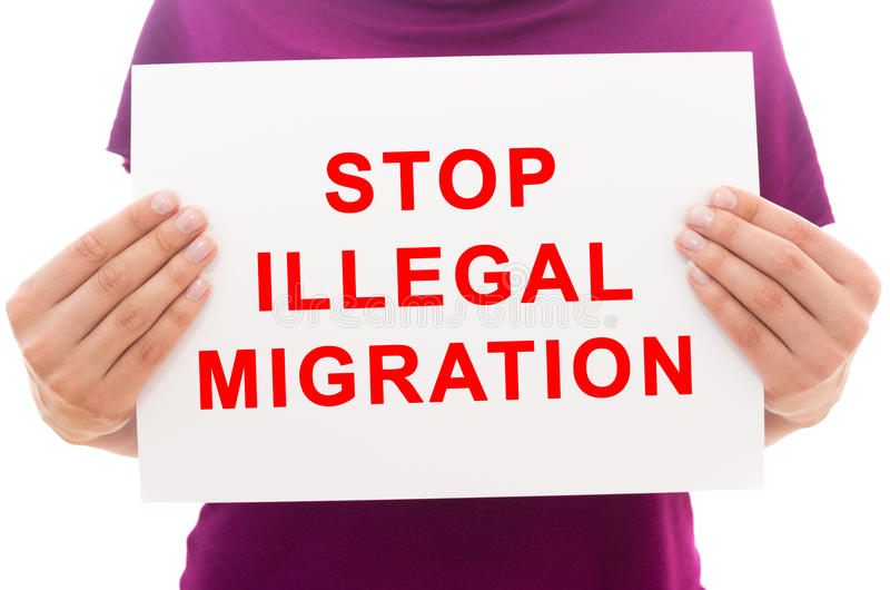 Stop illegal migration. Girl holding white paper sheet with text Stop illegal migration royalty free stock photo