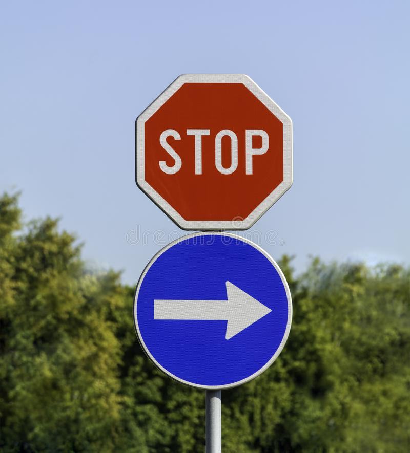 Stop and mandatory direction sign. Against blurred background - Road signs stop and moving direction royalty free stock photo
