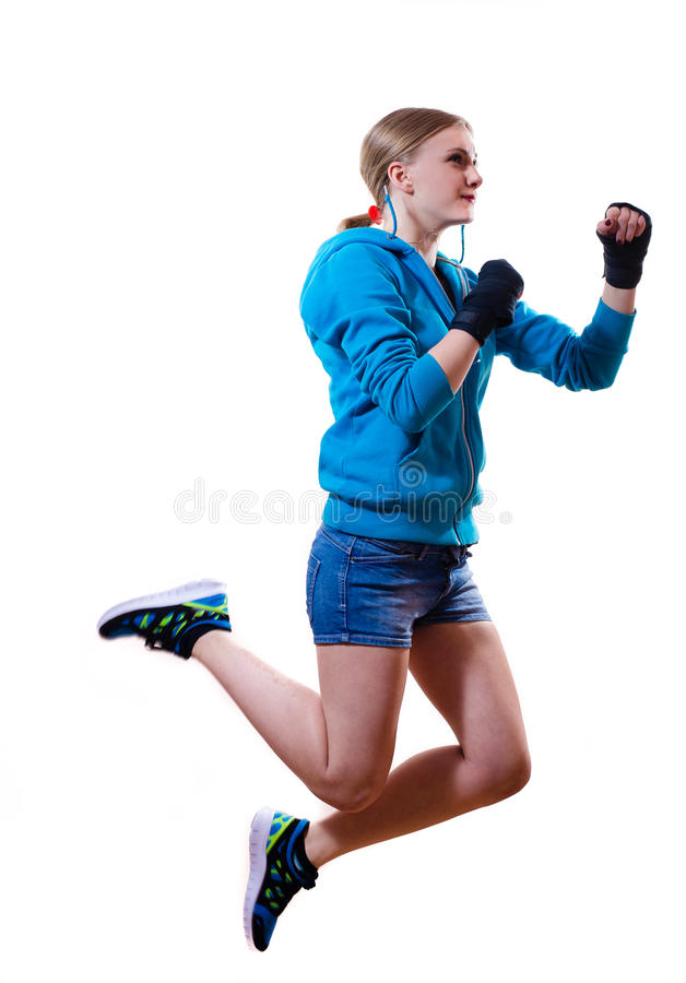 Stop motion: jumping high boxing blond girl. Isolated image of jumping high boxing blond young teenage girl in blue sweater and jeans shorts stock photo