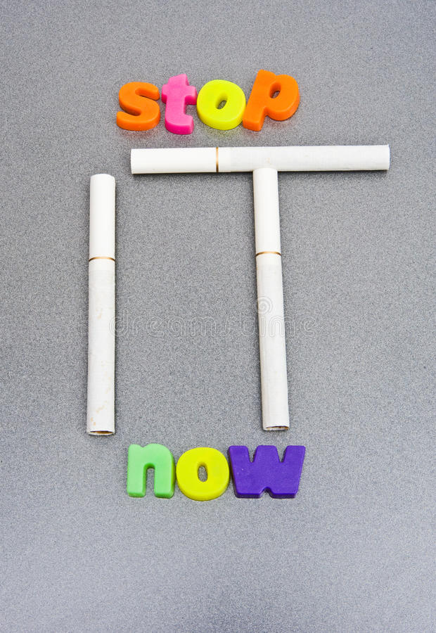Stop it now: smoking and health risk.. An image of the words ' stop it now' with the word ' it ' composed of three filter tip cigarettes. Because of the danger royalty free stock photo