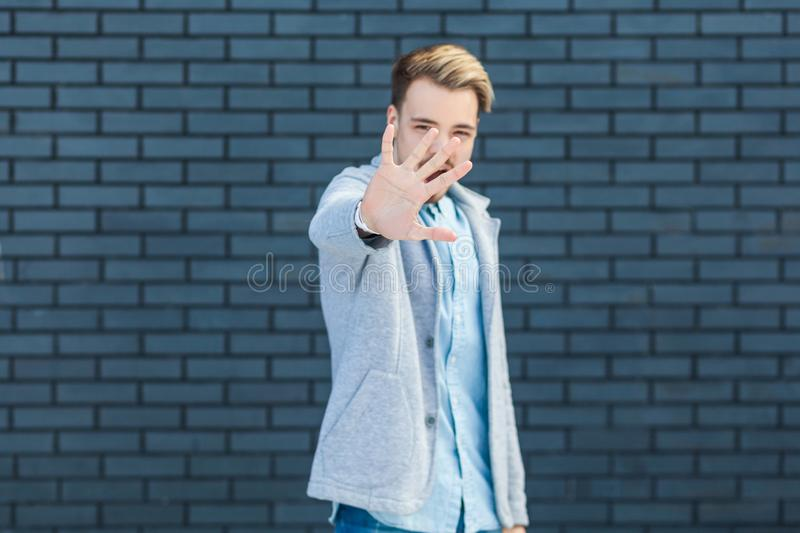 Stop! Portrait of anger handsome young blonde man in casual style standing with stop sign gesture and looking at camera, focus on. Hand. indoor studio shot on stock photography