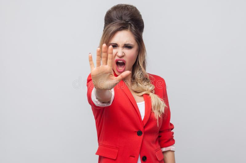 Stop! Portrait of angry beautiful business lady with hairstyle and makeup in red fancy blazer, standing with stop rejecting. Gesture and screaming. indoor royalty free stock photography