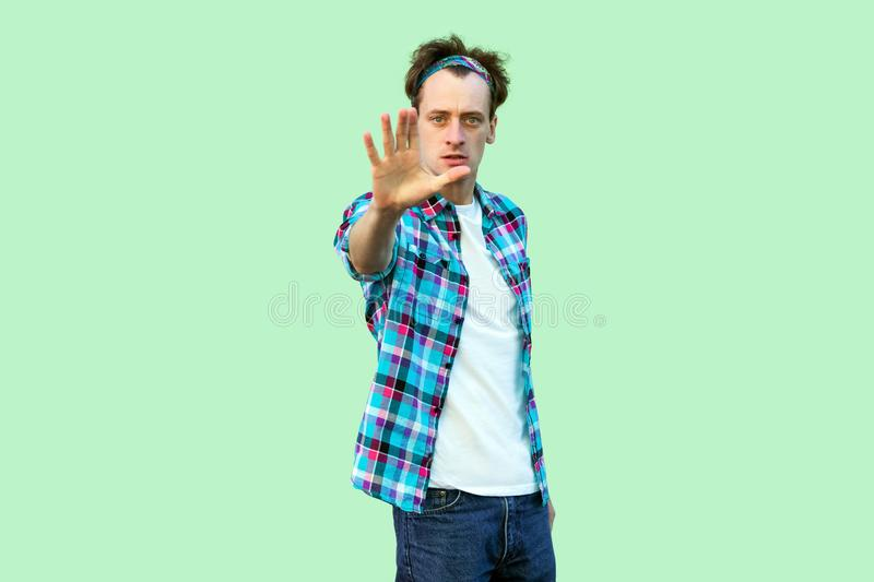 Stop it. Portrait of serious young man in casual blue checkered shirt and headband standing and showing stop with hand and looking stock photo