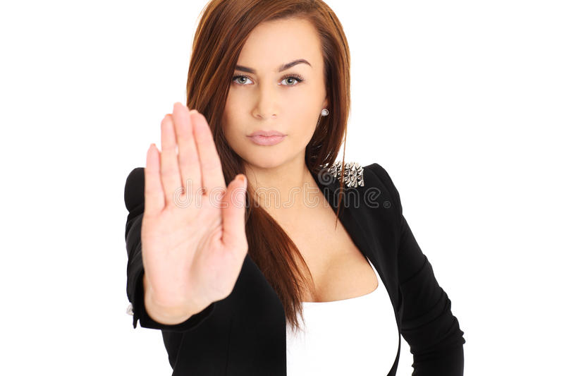 Stop!. A portrait of a young businesswoman showing a stop sign with her hand over white backgroud royalty free stock photography