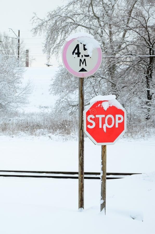 Stop. Red road sign is located on the motorway crossing the railway line in winter season.  stock photo