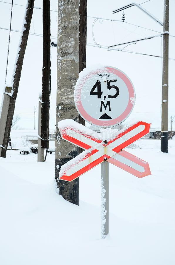 Stop. Red road sign is located on the motorway crossing the railway line in winter season.  royalty free stock image