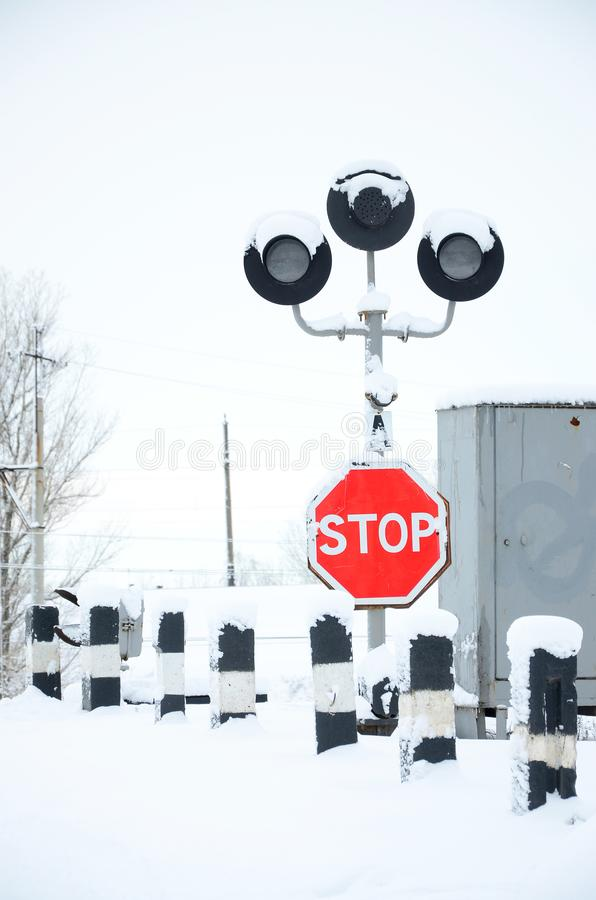 Stop. Red road sign is located on the motorway crossing the railway line in winter season.  royalty free stock photos