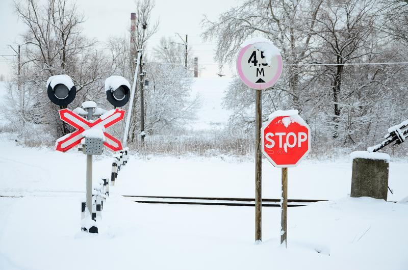 Stop. Red road sign is located on the motorway crossing the railway line in winter season.  stock photos