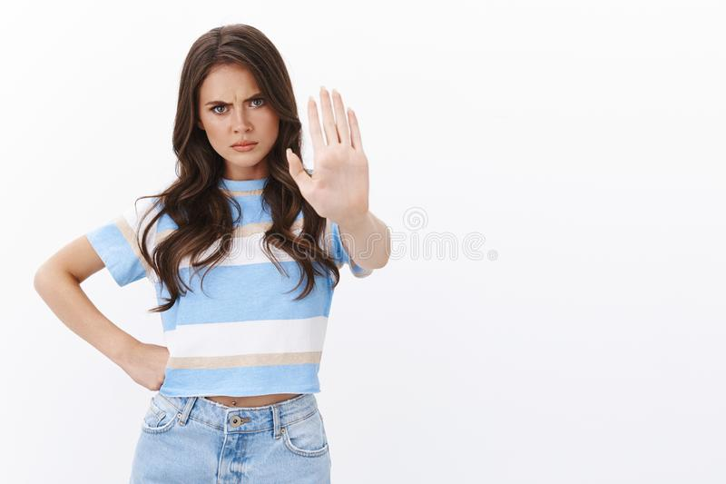 Stop right there. Serious-looking angry confident woman raise hand in prohibition, warn not trespass, frowning stare. Furious and persuasive, forbid misbehave stock photography