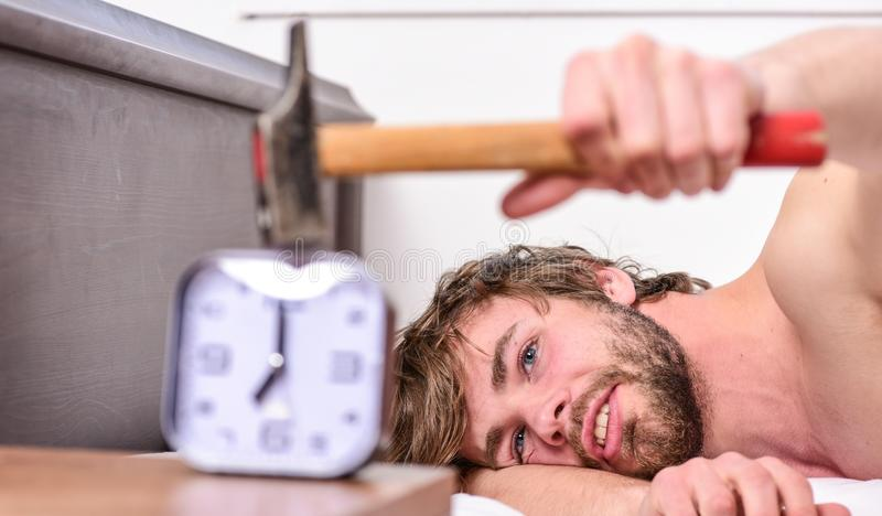 Stop ringing. Annoying ringing alarm clock. Man bearded annoyed sleepy face lay pillow near alarm clock. Guy knocking. With hammer alarm clock ringing. Break royalty free stock photos