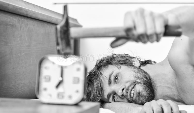 Stop ringing. Annoying ringing alarm clock. Man bearded annoyed sleepy face lay pillow near alarm clock. Guy knocking. With hammer alarm clock ringing. Break royalty free stock image