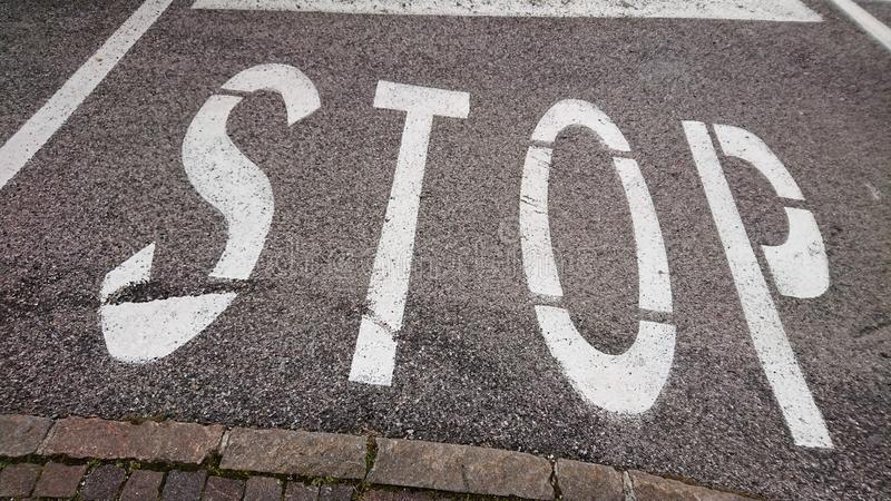 Stop Road Sign. A stop road sign painted in white on a side road stock photo