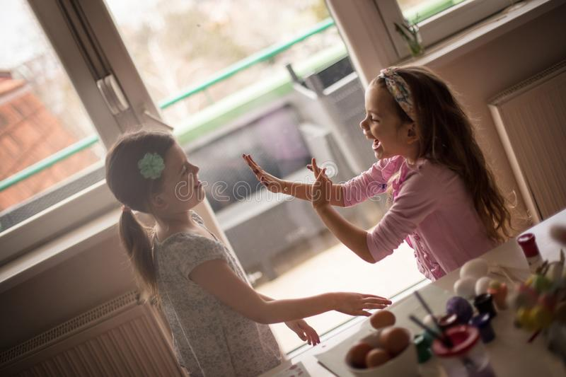 Stop, it it`s not nice to argue for Easter holidays. Little girls coloring Easter egg stock photography