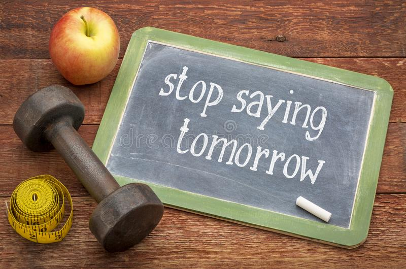 Stop saying tomorrow. White chalk text on a slate blackboard against weathered red painted barn wood with a dumbbell, apple and tape measure royalty free stock image