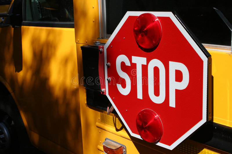 Stop for the School Bus. Yellow school bus and stop sign signalling all to pay attention to students crossing stock image