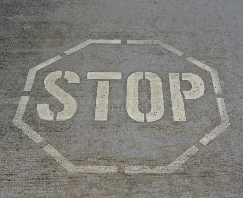 Stop sign on asphalt. Stop sign in white color on grey asphalt royalty free stock photography