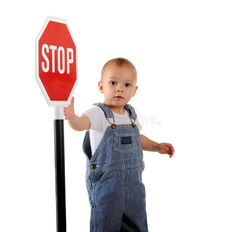 Stop Sign Baby. A one-year old looking at the viewer while displaying a stop sign. Isolated on white royalty free stock photos