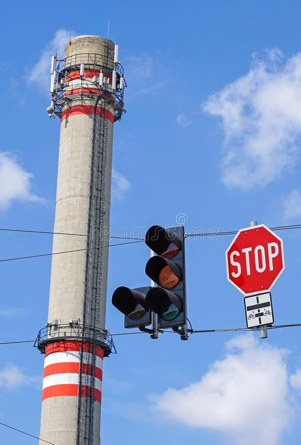 Stop sign and light next to the smoke stack of the power station royalty free stock photography