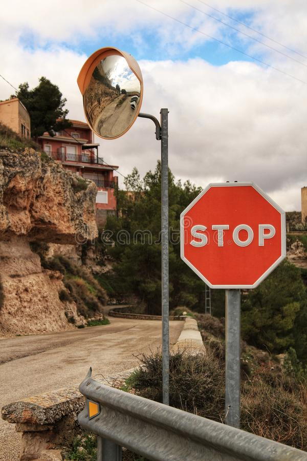 Stop sign and mirror panel on mountain road. In a cloudy day. Road surrounded by vegetation stock photos