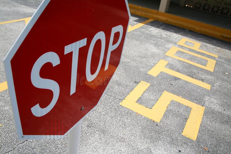 Stop Sign in Parking Lot. A stop sign sits on a small white post in a parking lot with painted yellow lines on the black asphalt stock image