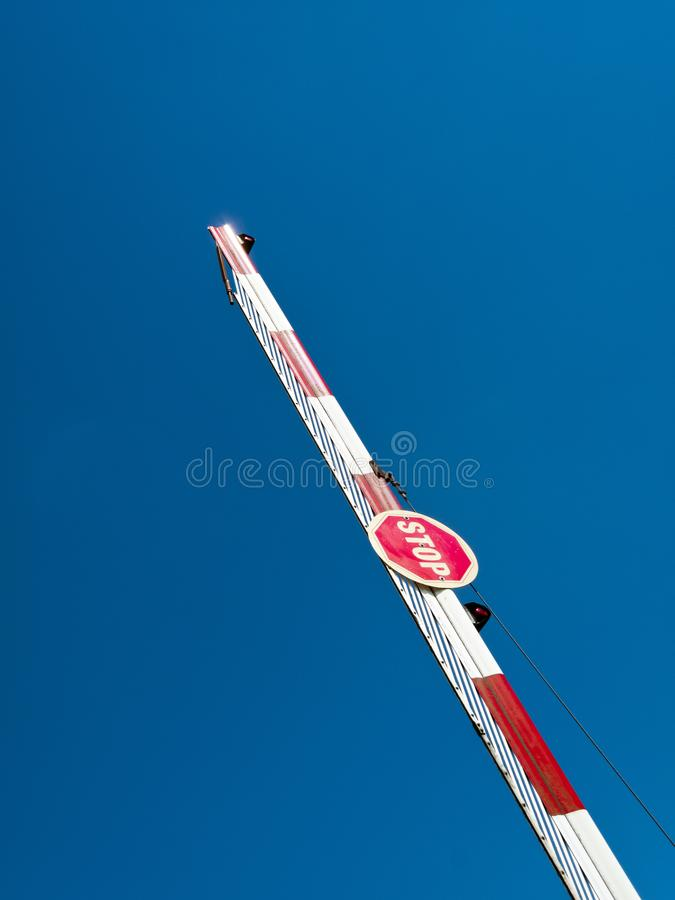 Stop sign. On a raised barrier against blue sky stock photos