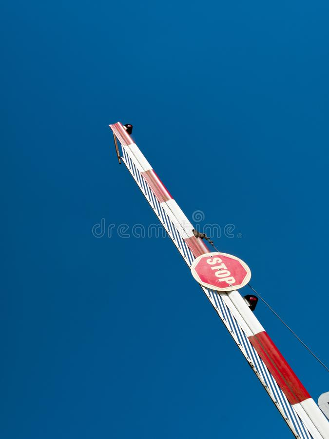 Stop sign. On a raised barrier against blue sky stock photography