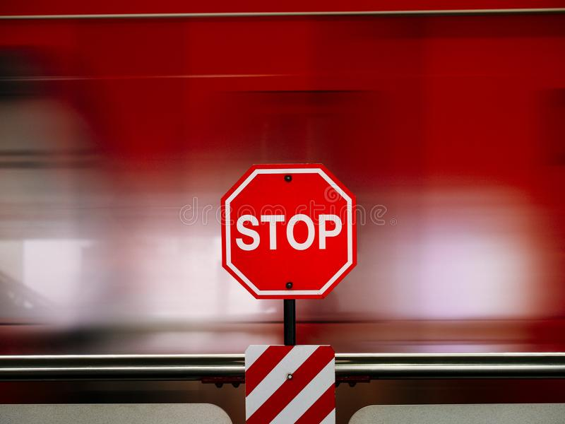 Stop sign in red against moving train blurry stock image