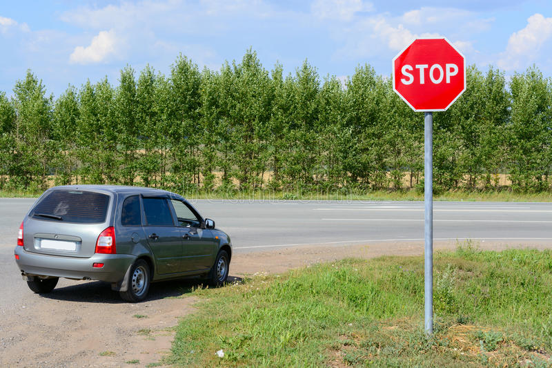 Stop sign on the road. And a car royalty free stock photos
