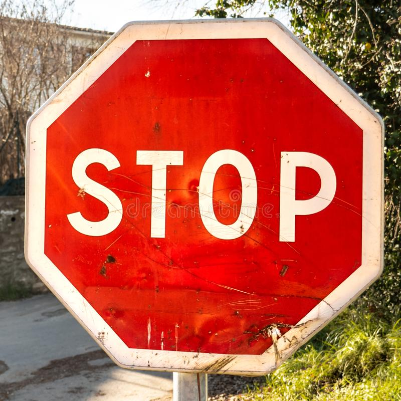 Stop sign on the road. Octagonal and a little broken old red stop sign on the road royalty free stock photos