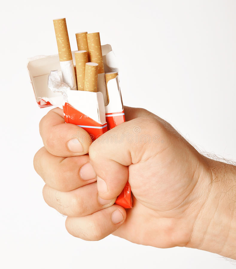 Stop smoking. Fist with crushed pack of cigarettes royalty free stock photography