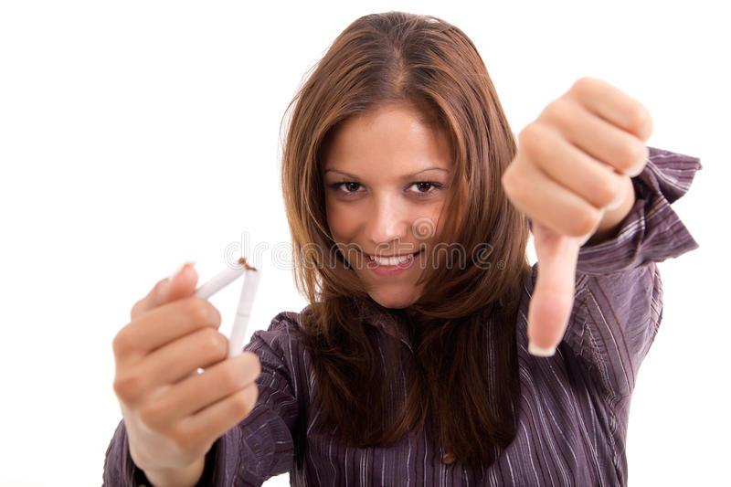 Stop smoking. Young woman breaking cigarette over white background stock photography
