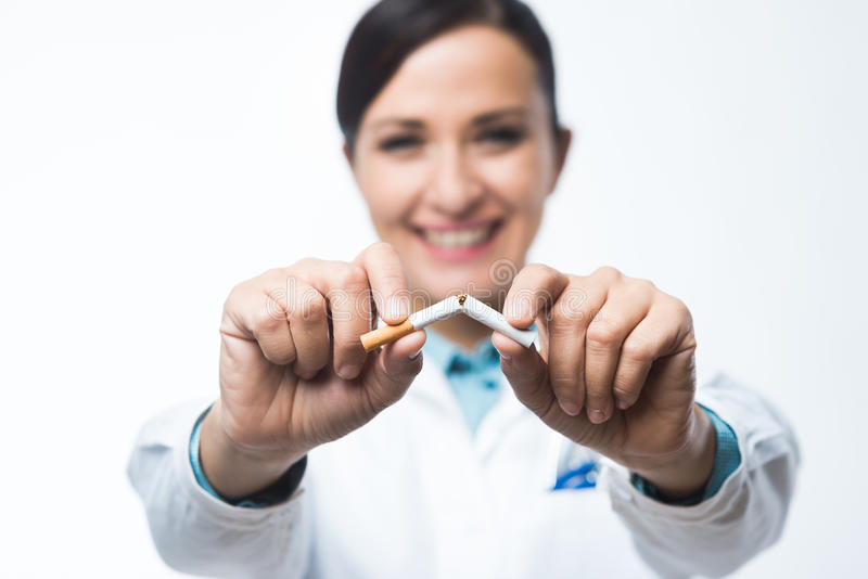 Stop smoking. Concept with female doctor breaking a cigarette royalty free stock photography