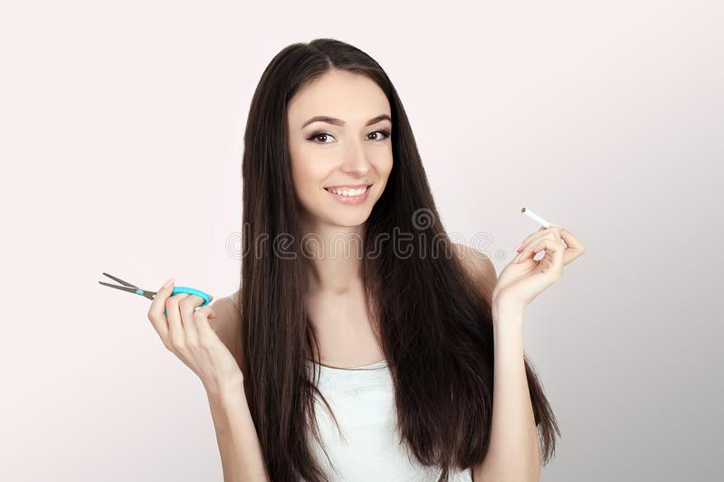 Stop smoking. Quit smoking Women`s hands holding a bunch of ciga. Rettes and cut them in half scissors. Stop smoking The concept of health. On a gray background stock images