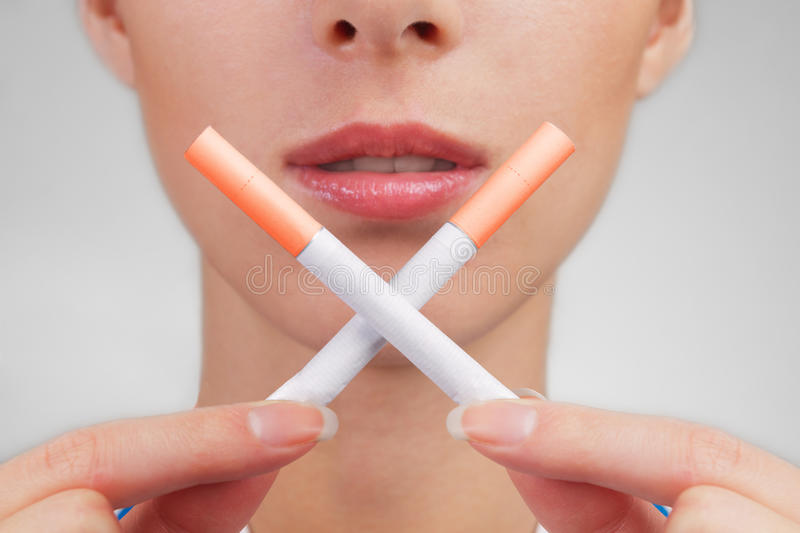 Stop smoking!. Woman holds two crossed cigarettes in front of her lips stock photography