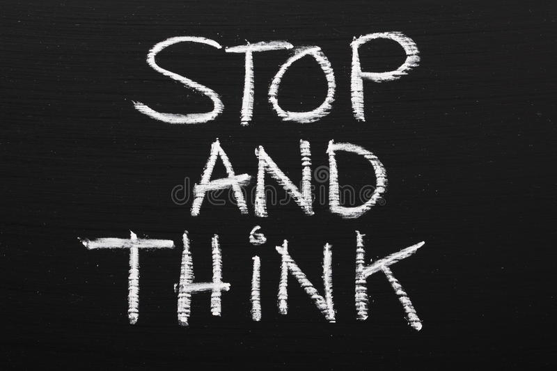 Stop and Think. The phrase Stop and Think written on a blackboard, as a reminder to take time out and think carefully before taking action royalty free stock image
