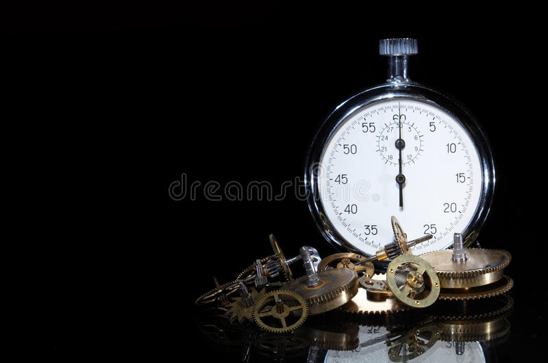 Stop Time. Gearwheels near standing stopwatch on dark background with copy space stock image