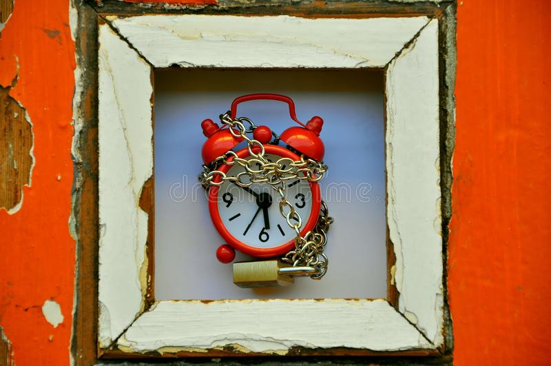 Stop the time concept. Ual image with an alarm clock and a chain with a locker royalty free stock photo