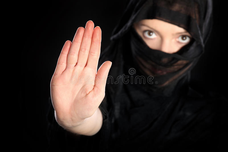 Stop to oppression. A picture of a young arabic woman showing to stop over black background royalty free stock photos