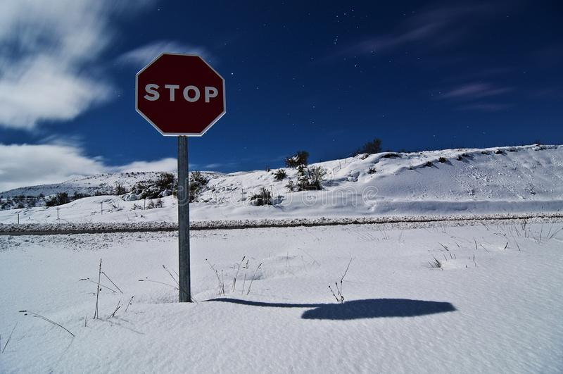 Stop traffic sign isolated on snowy peaceful landscape under moonlight starry night sky stock images