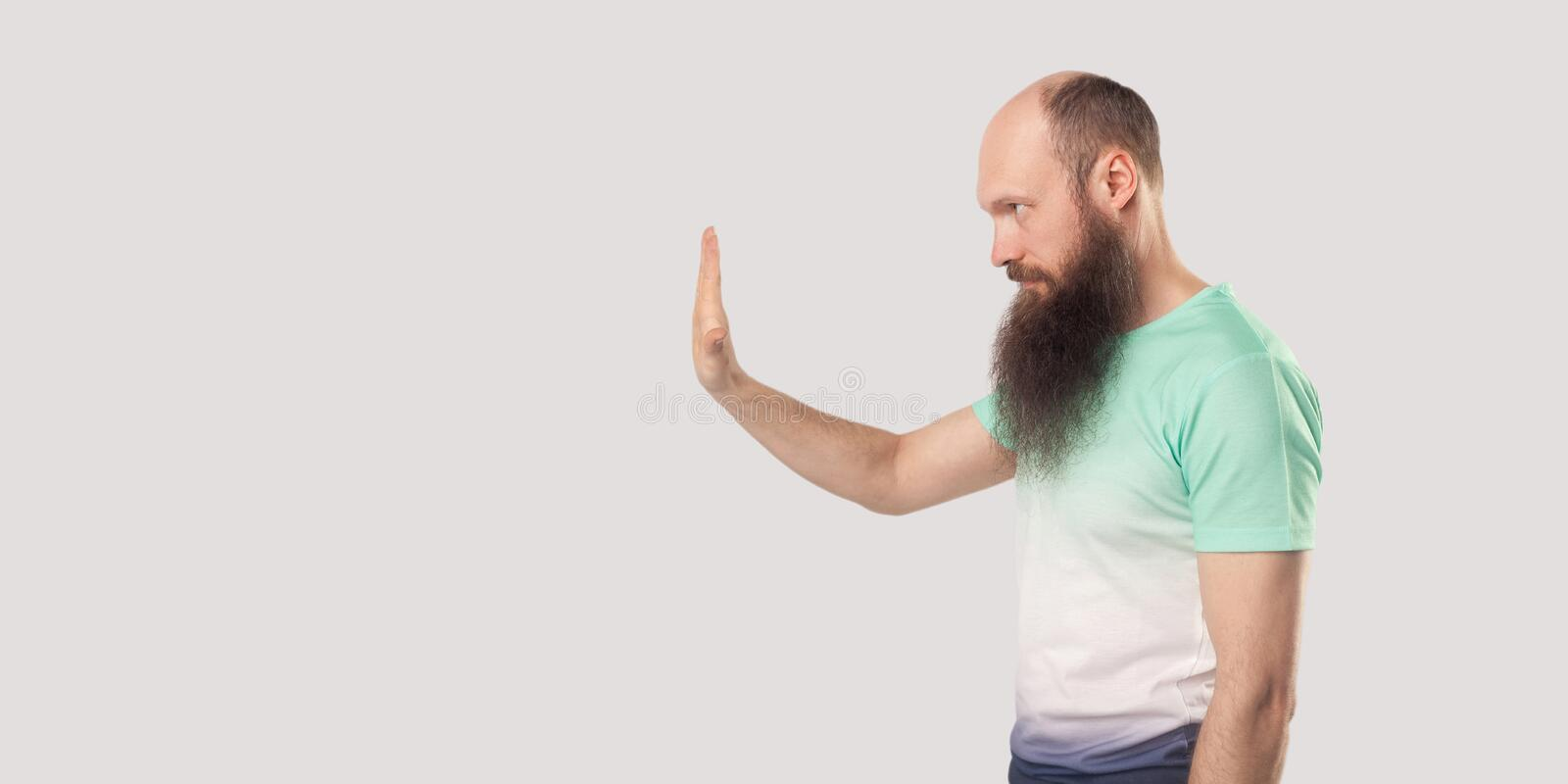 Stop, wait. Profile side view portrait of serious middle aged bald bearded man in green t-shirt standing with stop hand gesture. And looking forward. indoor royalty free stock images