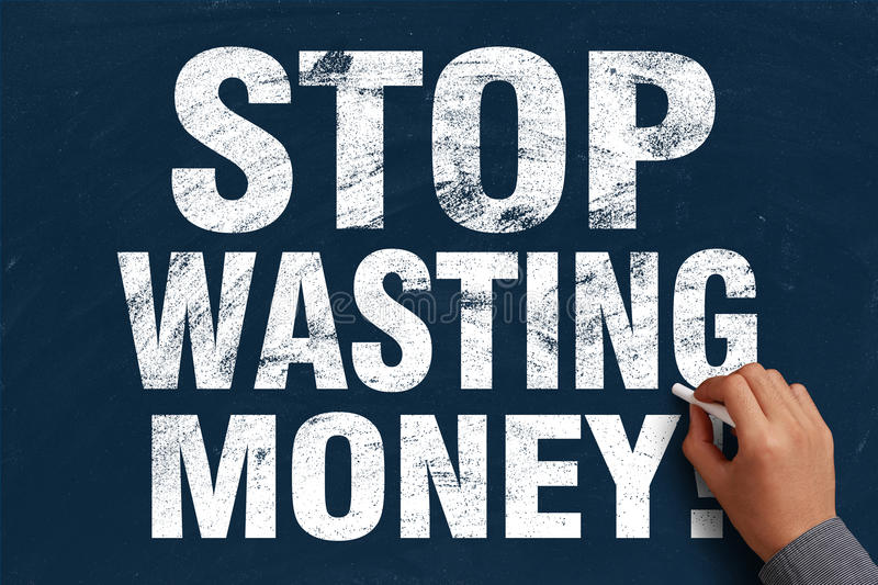 Stop Wasting Money. Businessman is writing Stop Wasting Money text on blue chalkboard stock photography