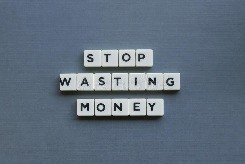 ' Stop Wasting Money ' word made of square letter word on grey background. Save, banking, financial, loan, success, debt, spend, profit, growth, risk royalty free stock photography